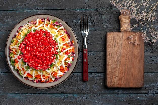 Vista dall'alto cibo natalizio gustoso piatto natalizio con semi di melograno accanto alla forchetta e tagliere sul tavolo grigio