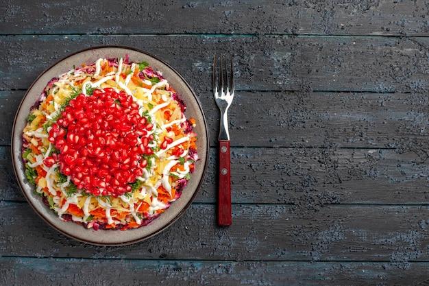 Vista dall'alto cibo natalizio gustoso piatto natalizio con semi di melograno accanto alla forchetta sul lato sinistro del tavolo grigio