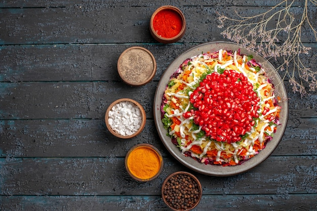 Top view christmas food white plate of christmas dish with seeds of pomegranate next to the tree branches and bowls of colorful spices on the table