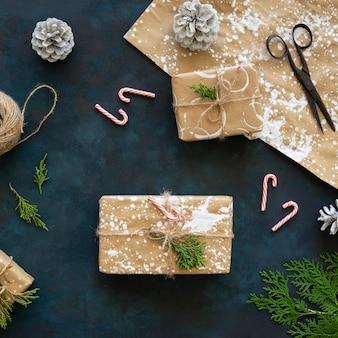 Vista dall'alto di regali di natale con pigne e bastoncini di zucchero