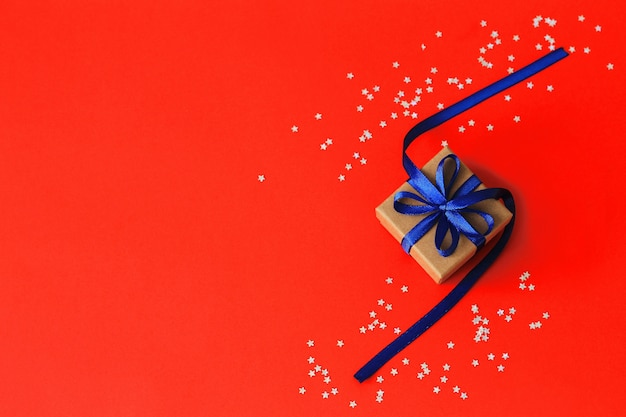 Top view on christmas gifts with ribbon on red paper background with silver stars. copyspace.