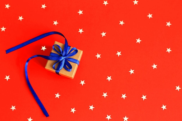 Top view on christmas gifts with ribbon on red paper background with silver stars