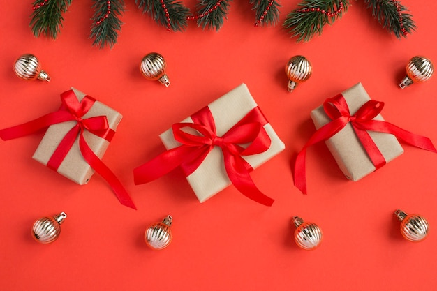 Top view of  christmas gifts with tiew red bow on the red background. close-up.
