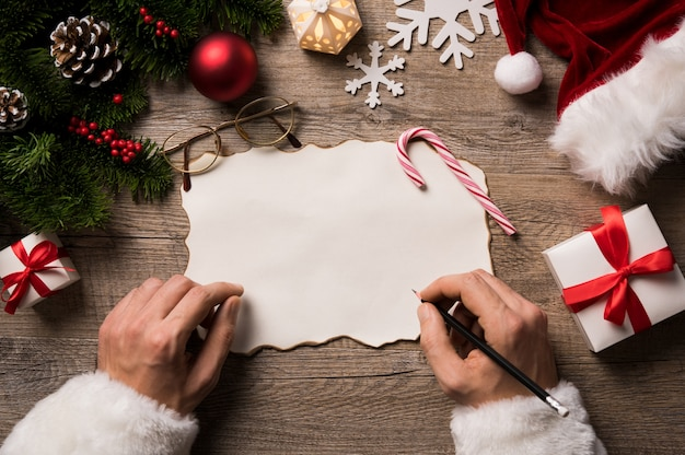 Top view of christmas letter in santa claus hand.