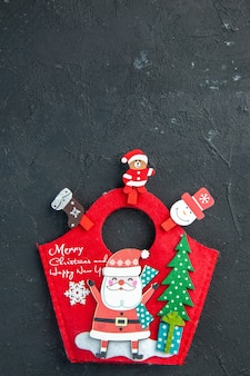 Top view of christmas mood with decoration accessories and new year gift box on dark surface