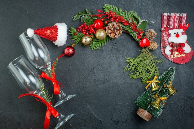 Top view of christmas mood with fallen glass goblets fir branches xsmas tree sock santa claus hat on dark background