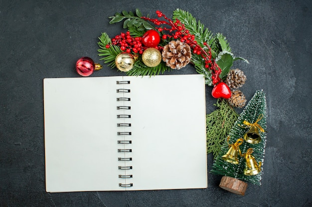 Top view of christmas mood with fir branches xsmas tree next to spiral notebook on dark background