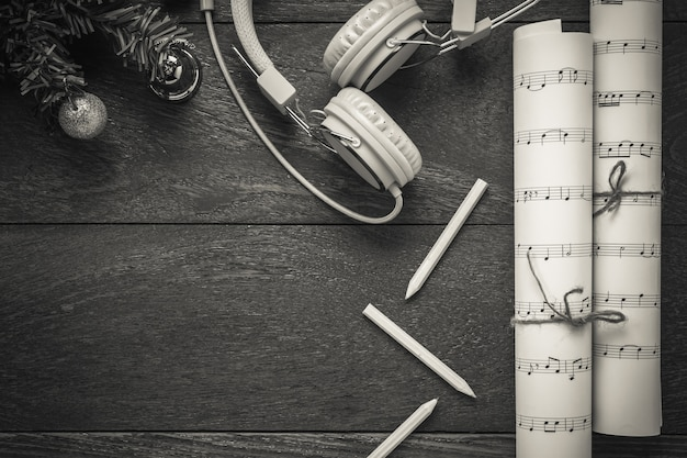 나무 테이블 배경에 크리스마스 장식과 헤드폰 상위 뷰 크리스마스 음악 메모 용지.이 음악 메모 용지를 직접 만듭니다.