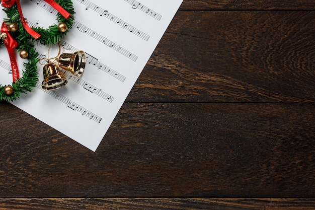 Top view christmas music note paper  with christmas wreath on wooden background and copy space.