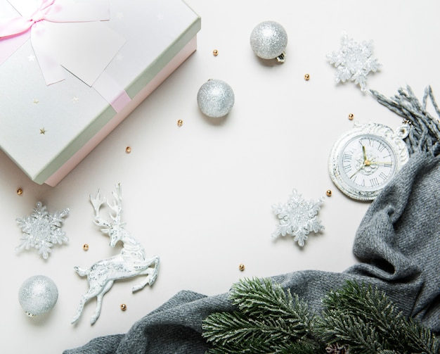 Top view christmas or new year composition on a grey and white background with white and silver christmas decorations, deer, snowflakes, balls and  clock