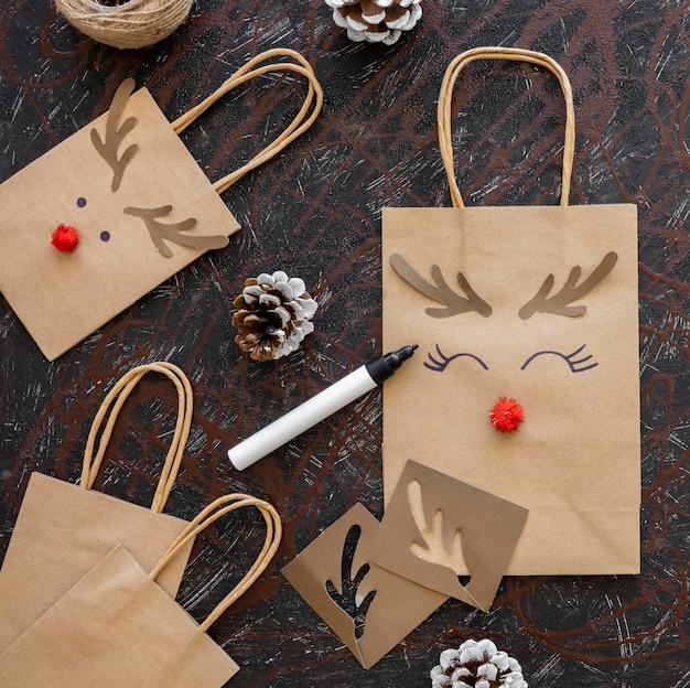 Vista dall'alto di sacchetti di carta natalizi con decorazioni di renne
