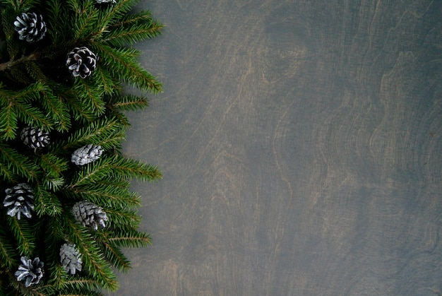Top view of christmas pine with silver cones on black wooden background