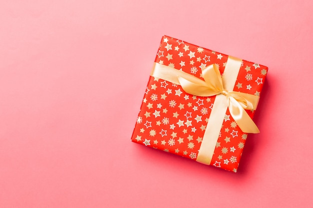 Top view christmas present box with gold bow on living coral background with copy space