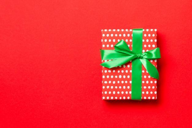 Вид сверху коробка подарка на рождество с зеленым бантом на красной предпосылке с космосом экземпляра.
