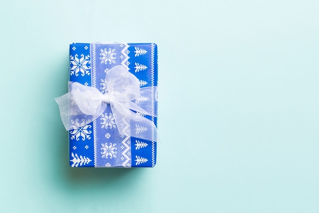 Top view christmas present box with white bow on blue background with copy space