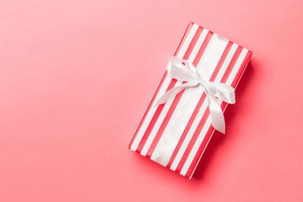 복사 공간이 있는 살아있는 산호 배경에 흰색 활이 있는 상위 뷰 크리스마스 선물 상자.