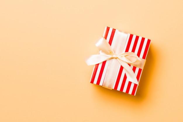 복사 공간이 있는 주황색 배경에 노란색 활이 있는 위쪽 보기 크리스마스 선물 상자.