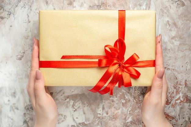 Vista dall'alto regalo di natale legato con fiocco rosso su bianco regalo di capodanno foto vacanza colore natale