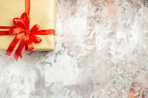 Vista dall'alto regalo di natale legato con fiocco rosso su foto bianca vacanza colore regalo di capodanno posto libero per il testo