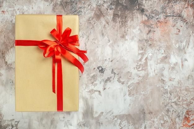 Vista dall'alto regalo di natale legato con fiocco rosso su foto bianca vacanza colore regalo di capodanno natale posto libero