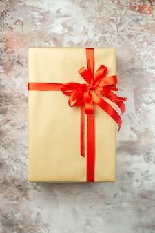 Vista dall'alto regalo di natale legato con fiocco rosso su foto bianca vacanza colore regalo di capodanno natale