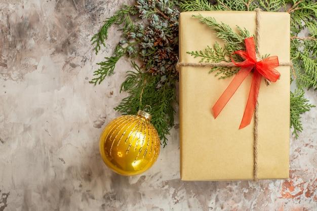 Vista dall'alto regalo di natale con ramo verde su bianco regalo di festa colore capodanno natale