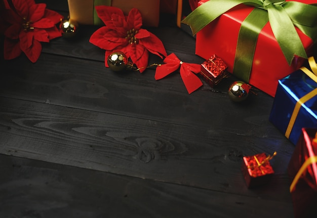 Top view of christmas presents on black wood. room for text