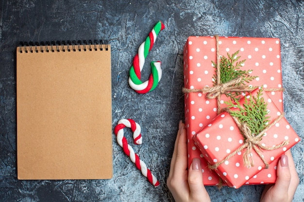 Top view christmas presents, candy cane and empty notebook