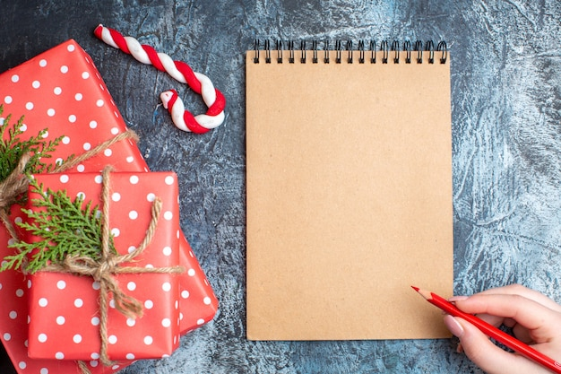 Top view christmas presents with empty notebook