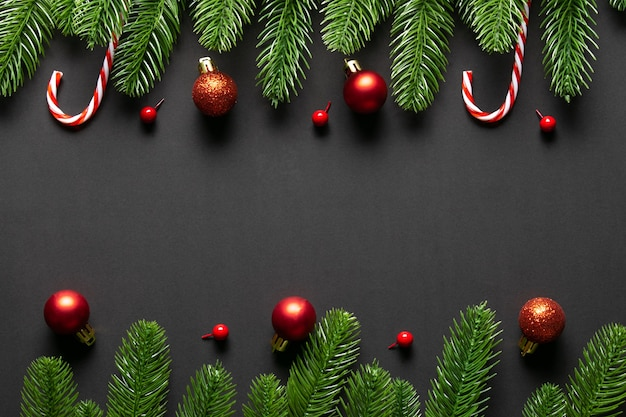Top view of christmas red balls with spruce  branches on black wooden background. copy space.