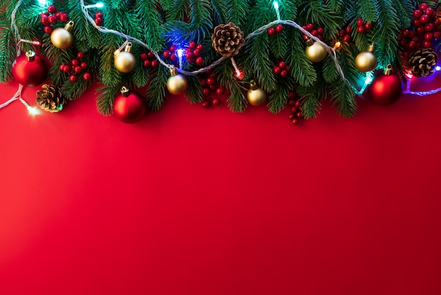 Top view of christmas spruce branches, pine cones, red berries and bell on red background.