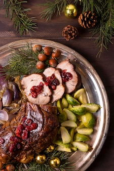 Vista dall'alto della bistecca di natale sulla piastra con decorazioni di pigne