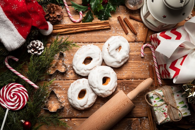 Top view christmas sweets with wooden background