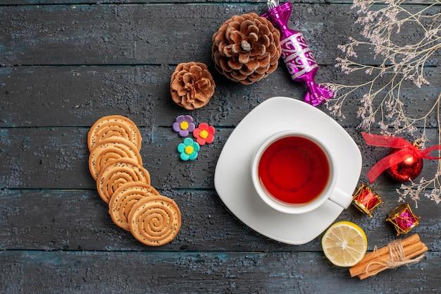 테이블에 쿠키 계피 스틱과 레몬이 있는 접시에 있는 차 한 잔 옆에 있는 크리스마스 장난감 나무 가지 상위 뷰