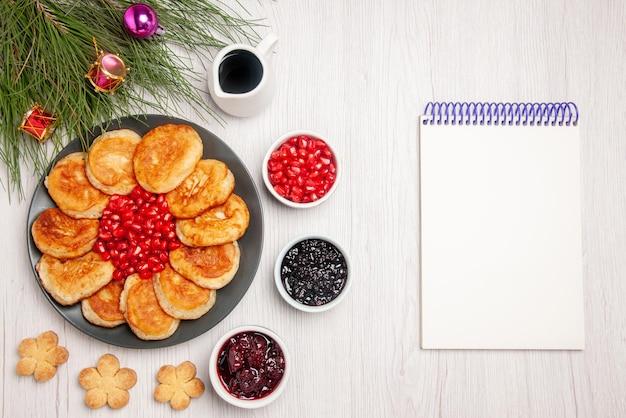 Vista dall'alto semi di albero di natale di melograno e frittelle nel piatto accanto alle ciotole di frutti di bosco accanto ai biscotti del taccuino bianco e albero di natale con i giocattoli dell'albero sul tavolo