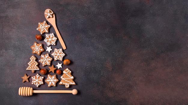Vista dall'alto della forma dell'albero di natale fatta di biscotti di panpepato e utensili da cucina con spazio di copia