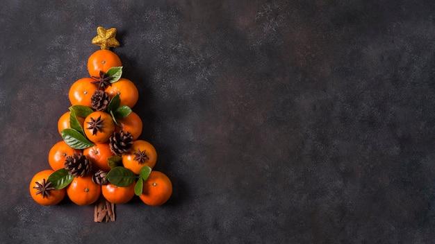 Vista dall'alto della forma dell'albero di natale fatta di mandarini e pigne con spazio di copia