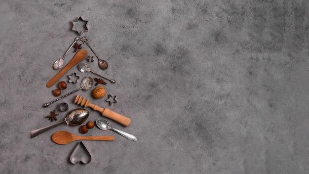 La vista superiore della forma dell'albero di natale fa degli utensili da cucina con lo spazio della copia