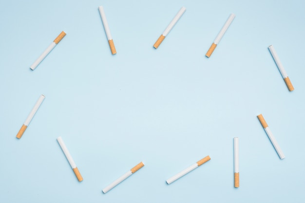 Top view of cigarettes arranged on blue background