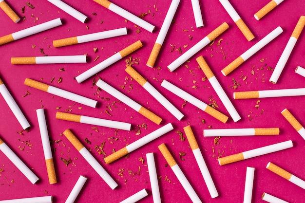 Вид сверху сигарет на розовом фоне