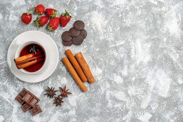Vista dall'alto tè alla cannella ai semi di anice e alcune fragole cioccolatini cannellini semi di anice sul lato sinistro del tavolo con spazio libero