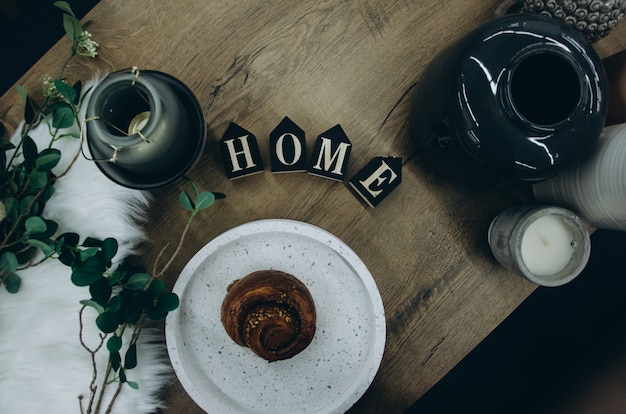 Top view of cinnamon bun on white dish, vase, green plant, candle in a candlestick and letters home