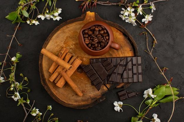 Кофе сверху шоколад корицы на коричневый стол на темном