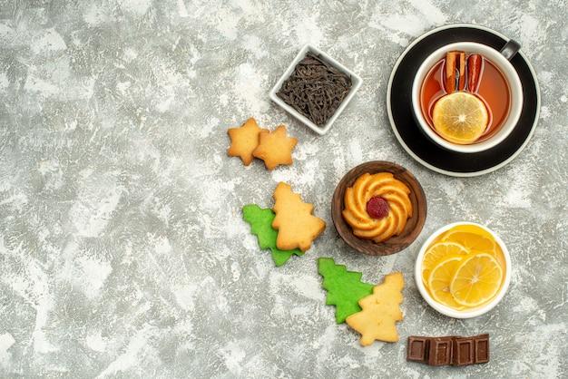 Ciotole di biscotti da tè al limone e cannella con vista dall'alto con fette di limone e cioccolato sulla superficie grigia della copia
