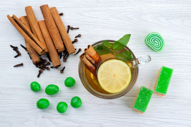Una vista dall'alto cannella e tè con limone e marmellata sulla scrivania bianca, tè dolce caramelle