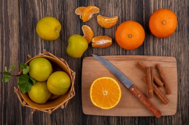 Vista dall'alto cannella con fetta d'arancia e coltello sul tagliere con prugna in cestino su sfondo di legno