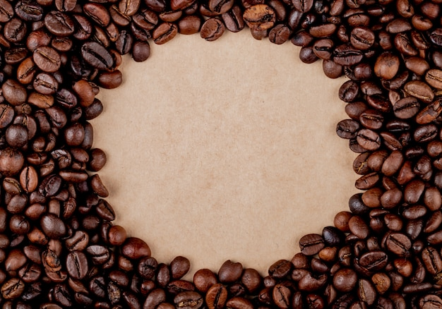 Top view of circle coffee beans on brown paper texture background