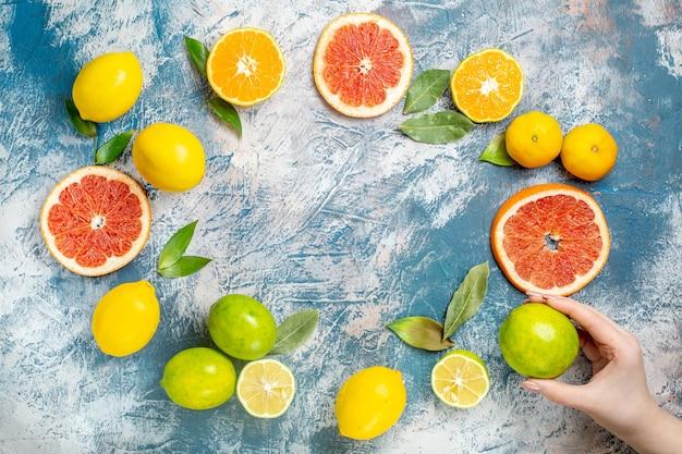 Vista dall'alto cerchio fila agrumi limoni tagliati pompelmi mandarini limone in mano di donna sul tavolo bianco blu