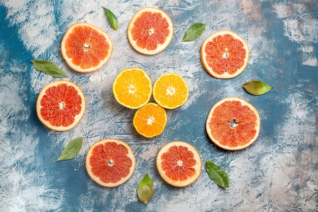 Top view circle row cut grapefruits cut oranges blue white table