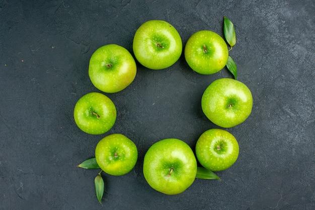 暗いテーブルの上のビュー円列青リンゴ